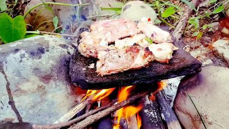 农村大叔在河边做美食,用石板和大火烤猪排吃,太好吃了
