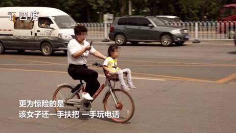 别拿生命当儿戏!孩子坐车筐 骑车玩手机 网友:简直是混账行为