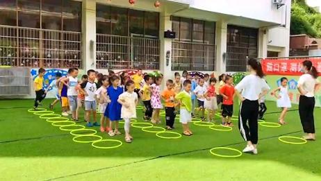 幼儿园老师教小朋友跳圈圈,样子萌萌真可爱,我也想学