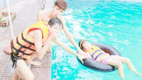 儿童扮演游戏:正在睡觉的小女孩被扔进游泳池,在水面上漂浮着